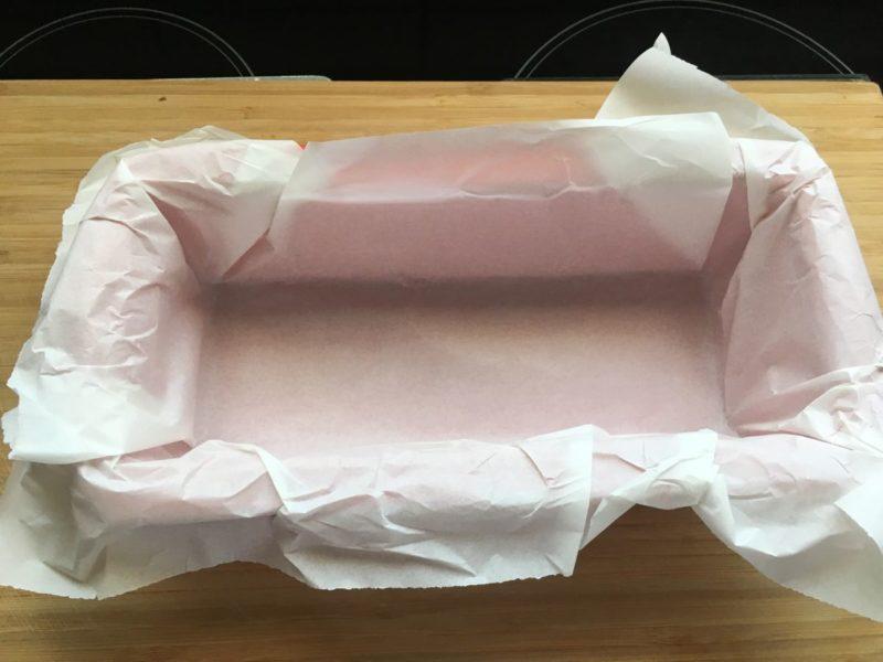 Die Form mit Butterbrot- oder Backpapier auskleiden